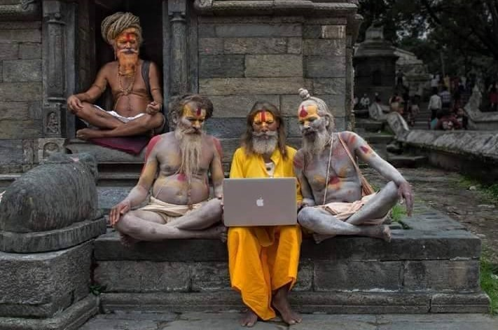 Brahmin sit outside a temple with a MacBook.